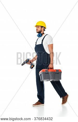 Handsome Workman In Overalls And Hardhat Holding Toolbox And Electric Screwdriver While Walking On W