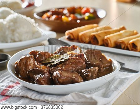filipino pork adobo in bowl with rice in background