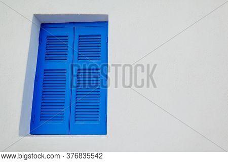Typical Architecture In Akrotiri Village On Santorini Island, Greece. White House With Blue Window.