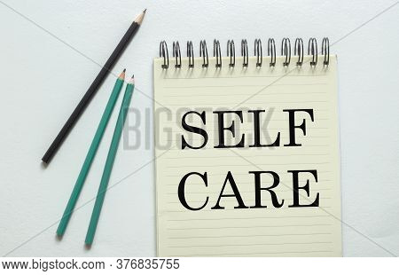 Two Green One Black Pencil With Text Self Care In The Notebook On The White Background