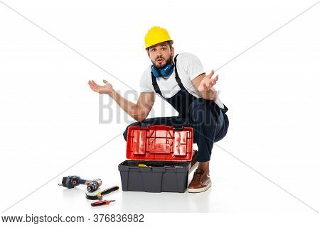 Confused Workman Showing Shrug Gesture Near Tools And Toolbox On On White Background
