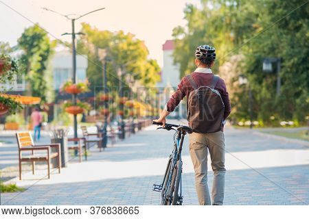 Male Commuter Wearing Bike Helmet Walking Away. Safe Cycling In City, Bicycle Commuting, Active Urba