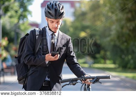Portrait Of A Male Commuter In A Suit And Bicycle Helmet With A Phone. Cycling Around The City, Goin