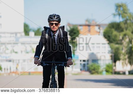 Portrait Of A Male Commuter Riding A Bicycle. Cycling Around The City, Going To Office Work By Bike