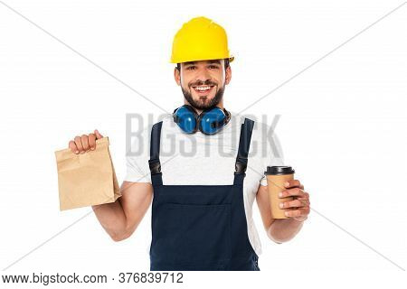 Handsome Workman Holding Coffee To Go And Paper Bag And Smiling At Camera Isolated On White