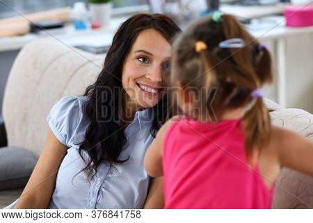 Portrait Of Smiling Woman And Child Sitting On Sofa. Cheerful Mum Having Fun With Kid At Home. Happy