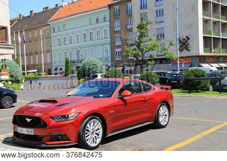 American Sports Car Red Ford Mustang With The Emblem Horse On The Hood Is Standing On A Street In Th