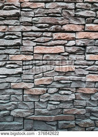 The Texture Of Narrow Flat Stones In Gray-brown Tones. Abstract Stone Wall Background For Designers.