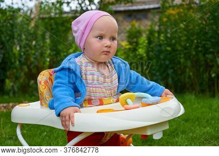 Baby Sitting In A Walker On The Grass, Baby In The Backyard Sitting In A Walker On The Lawn Grass
