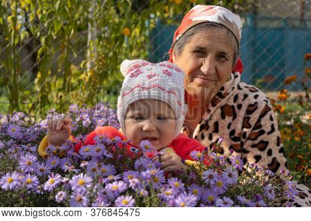Grandmother With Baby In Autumn Flower Garden, Autumn Portrait Of Grandmother With Granddaughter In