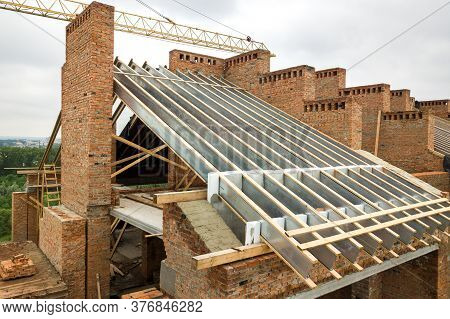Unfinished Brick Apartment Building With Wooden Roof Structure Under Construction.