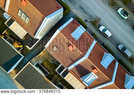 Aerial View Of Residential Houses With Red Roofs And Streets With Parked Cars In Rural Town Area. Qu