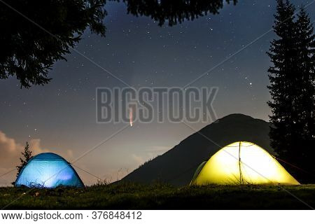 Two Brightly Lit Tourist Tents On Forest Clearing In Mountains With Starry Sky And Neowise Comet Wit