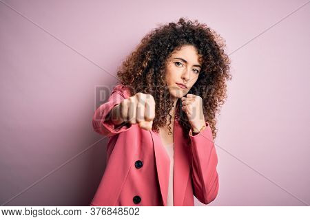 Young beautiful businesswoman with curly hair and piercing wearing elegant jacket Punching fist to fight, aggressive and angry attack, threat and violence