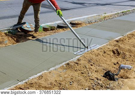 Laying Down New Sidewalk In Wet Concrete On Freshly Poured Sidewalks