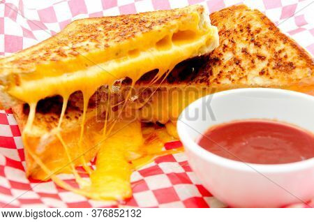 Decadent Grilled Cheese Sandwiches With Oozing Cheese Running Out With Ketchup For Dipping