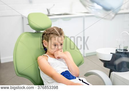 Little Girl Looks Worried With Fear Closes Mouth With Handssitting In A Dental Chair. Visiting Denti
