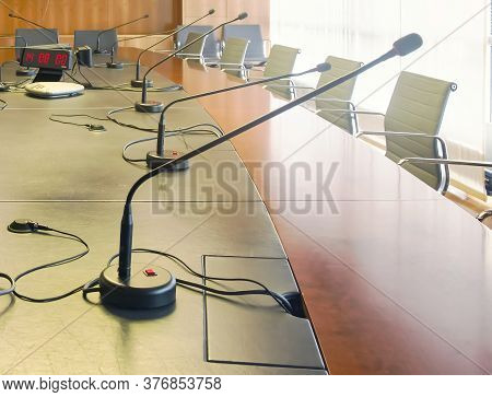 Microphone On A Wooden Table And Empty Chairs In A Boardroom. Auditorium, Meeting.