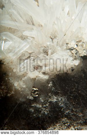 Quartz Mineral On A Black Background Showing Iron Pyrite