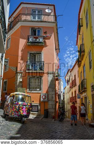 Lisbon, Portugal - 22 August 2018: Narrow Streets With Colorful Buildings And A Tourist Car (tuk Tuk