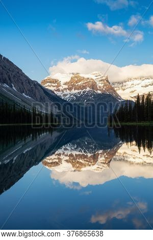 View Of Beautiful Marvel Lake Surrounded By Canadian Rocky Mountains During Cloudy Sunrise. Located