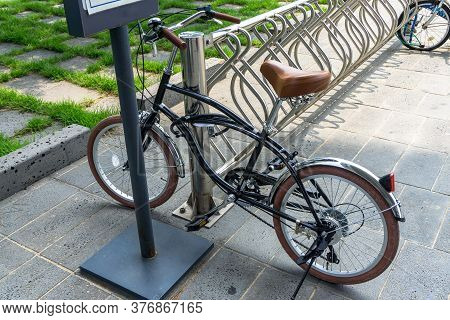 Glossy Black Vintage Bicycle Parks At The Bicycle Park With Anti-theft Bike Lock Cable Hook Up To Th