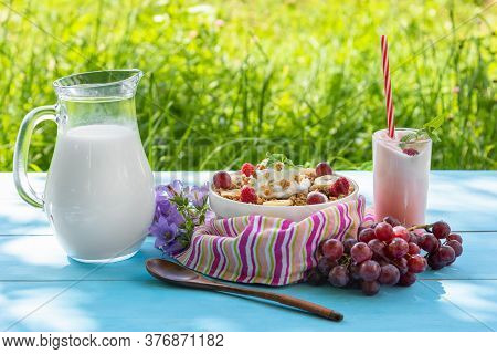 Summer Breakfast Porridge With Raspberries, Grapes And Delicious Yogurt With A Straw On A Blue Table