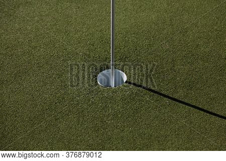A Golf Hole With Flag And Artificial Grass
