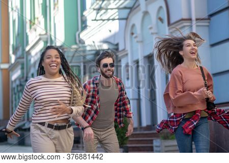 Guy And Two Girls Running Bouncing Down The Street