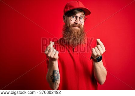 Young handsome delivery man wearing glasses and red cap over isolated background doing money gesture with hands, asking for salary payment, millionaire business
