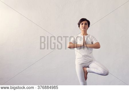 Young And Fit Woman Practicing Yoga Indoor In The Class. Stretching Exercise In The Day Light. Sport