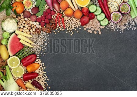 Vegan super food background border with a large collection of foods. High in protein, anthocyanins, vitamins, minerals, antioxidants, fibre, omega 3 and smart carbs .Ethical eating concept. Flat lay.