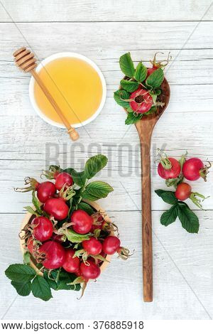 Rosehip berry fruit health food used in herbal medicine for a cold & flu remedy drink with honey for immune system boost high in antioxidants & vitamin c. Flat lay on rustic wood background.