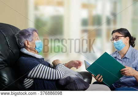 A Companion Or A Caregiver Of An Elderly Woman Talking, Reading Books. Both Wear Face Protective Mas
