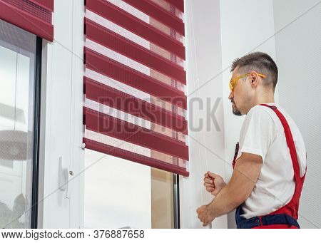 A Handyman In A Uniform Pull Rope And Closed Modern Jalousie