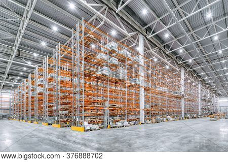 Large Industrial Warehouse. Tall Racks Are Completely Filled With Boxes And Containers. Many Cardboa