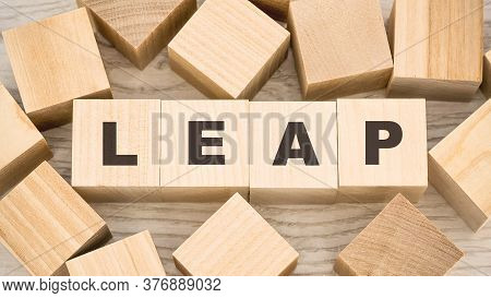 Word Leap With Black Letters On Toy Wooden Cubes And Numerous Blank Details On Light Table View From