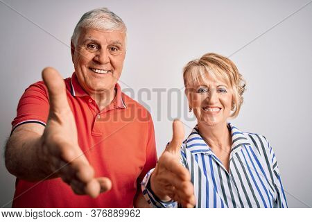 Senior beautiful couple standing together over isolated white background smiling friendly offering handshake as greeting and welcoming. Successful business.
