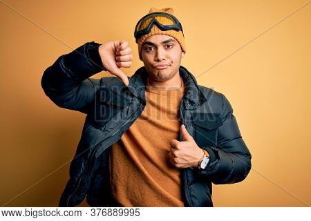 Young brazilian skier man wearing snow sportswear and ski goggles over yellow background Doing thumbs up and down, disagreement and agreement expression. Crazy conflict