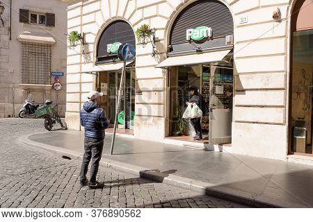 Rome, Italy - 12 March 2020: A Man Wait In Line Outside A Local Supermarket In Central Rome, Italy.