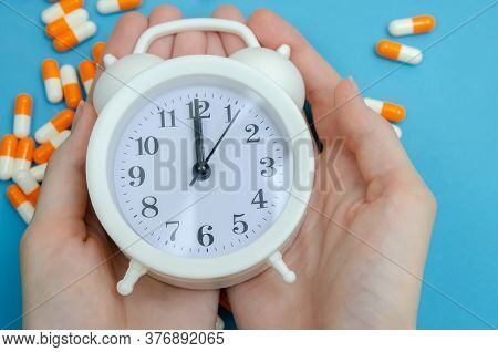 Women's Hands Hold A White Alarm Clock On A Background Of Scattered Tablets, Capsules On A Blue Back