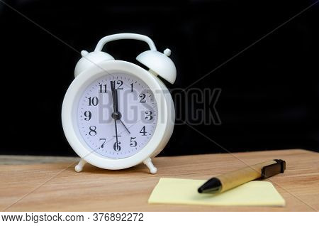 White Alarm Clock Stands On A Wooden Table With A Writing Sheet And A Pen Against A Black Wall, Copy