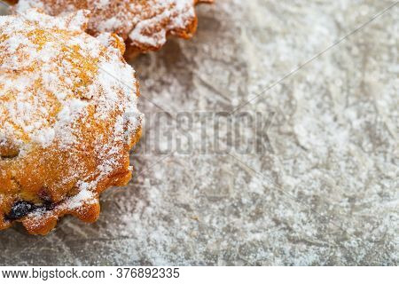 Close-up Of A Berry Cupcake Sprinkled With Powdered Sugar. Made At Home Dessert From Natural Product