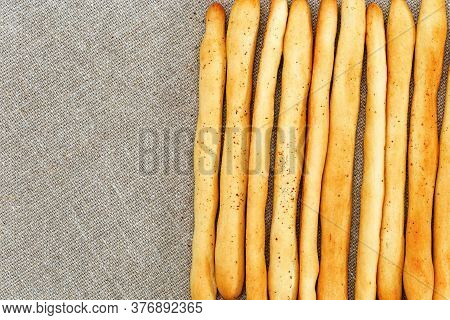 Background Of Breadsticks Stacked In Rows And Sackcloth. Long Bread Sticks Made Of Wheat Flour Lie O