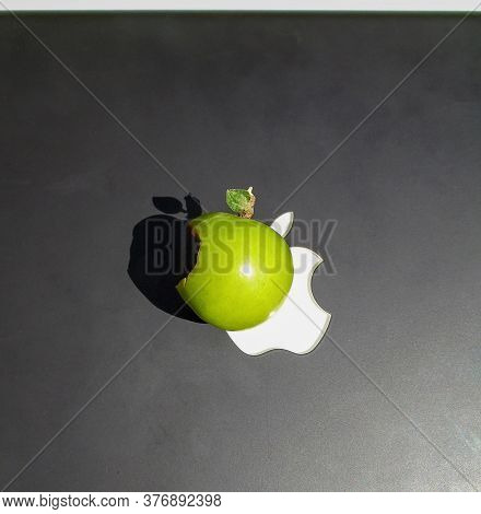 Green Nibbled Apple On A Black And White Background Close-up