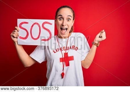 Lifeguard woman wearing t-shirt with red cross and whistle holding banner with sos message screaming proud and celebrating victory and success very excited, cheering emotion