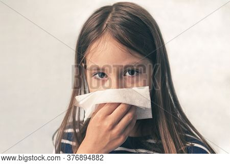 Caucasian Little Girl To Blow Her Nose With A Hygienic Wet Wipe. Seasonal Sickness. Child Sneezes In