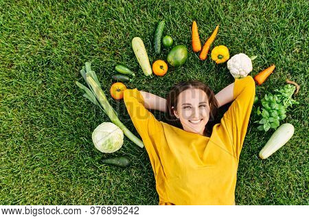 Top View Of Healthy Woman Surrounded Eco Vegetables On The Green Grass Outdoors. Happy Girl Lies On