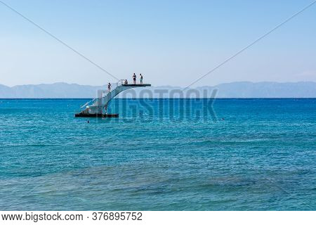Rhodes, Greece - May 13, 2018: People On A Sea Diving Platform. Elli Beach, The Main Beach Of Rhodes
