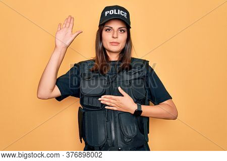 Young beautiful brunette policewoman wearing police uniform bulletproof and cap Swearing with hand on chest and open palm, making a loyalty promise oath
